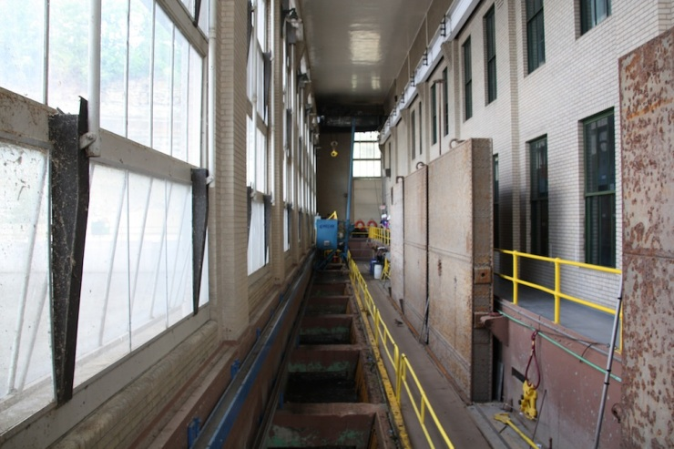 """The north side of the hydroelectric plant, where the water enters the facility (above the dam), also known as the """"penstock."""" The water is screened here to remove any foreign objects."""