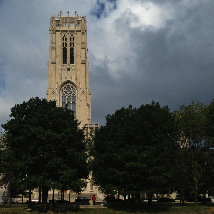 Clouds forming. Although the sky is dark, the limestone of the Scottish Rite shines brightly from behind the trees.