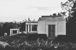 A view from the James Whitcomb Riley grave, viewing the graves at the top of the hill & the view of downtown Indianapolis.